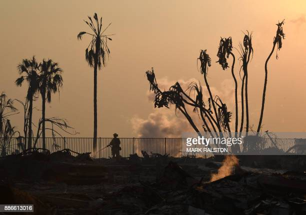 TOPSHOT A firefighter hoses down flareups at the two story Hawaiian Village Apartment complex that burnt to the ground during the Thomas wildfire in...