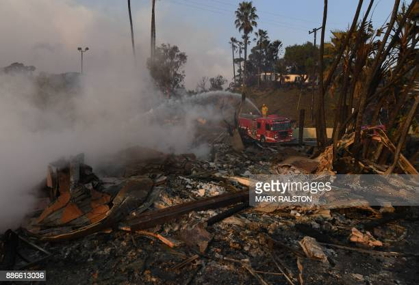 A firefighter hoses down flareups at the two story Hawaiian Village Apartment complex that burnt to the ground during the Thomas wildfire in Ventura...