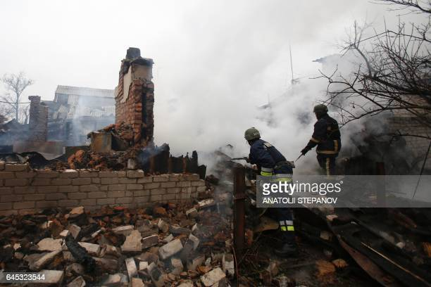 Firefighter inspect a fire in Avdiivka after heavy shelling by proRussian rebels on February 25 2017 Sixteen Ukrainian soldiers were wounded within a...