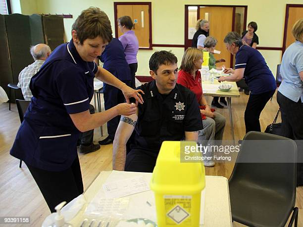 A firefighter is given an innoculation against Swine flu at a medical centre set up in Cockermouth Methodist Church on November 25 2009 in...