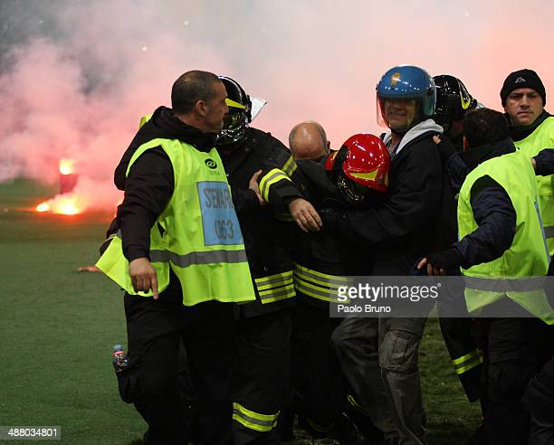 A firefighter is injured after been hit by a flare before the TIM Cup final match between ACF Fiorentina and SSC Napoli at Olimpico Stadium on May 3...