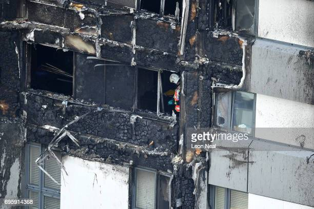 A firefighter is seen in a lower window of the burning 24 storey residential Grenfell Tower block in Latimer Road West London on June 14 2017 in...