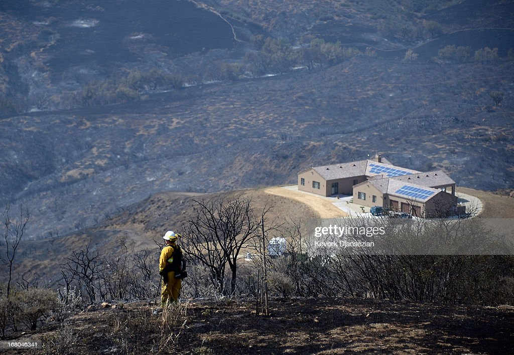 A firefighter keeps a lookout for hot spots in the charred landscape around a home which escaped damage from the Springs wildfire in Deer Creek on May 4, 2013 in Malibu, California. Nearly 1,000 firefighters continue to battle wind and dry conditions with over 28,000 acres burned and only 20% containment.