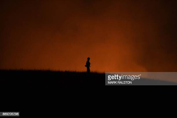 A firefighter keeps watch while a hill burns beside a housing estate as the Thomas wildfire continues to burn in Ojai California on December 9 2017...