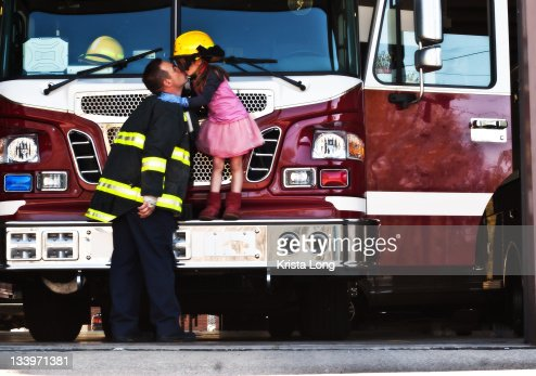 Firefighter kissing his young daughter : Stock Photo