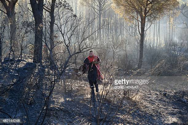 A firefighter leaves an area after fighting a wildfire in BagnolsenForet in the Var department in southern France on July 27 2015 Three campsites...
