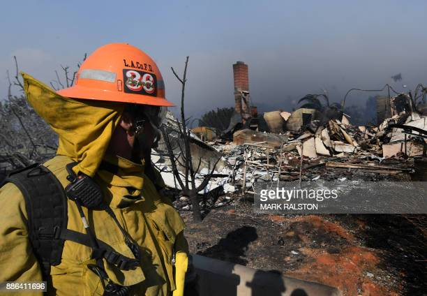A firefighter looks at a house burnt to the ground during the Thomas wildfire in Ventura California on December 5 2017 Fastmoving windfueled brush...