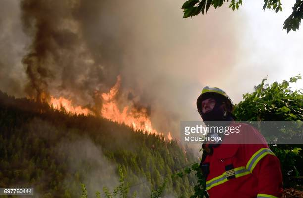 A firefighter looks on as he works to extinguish a wildfire in Carvalho next to Pampilhosa da Serra on June 19 2017 More than 1000 firefighters are...