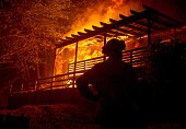 A firefighter looks on while a house is engulfed in flames during the Valley fire in Seigler Springs California on September 13 2015 The governor of...