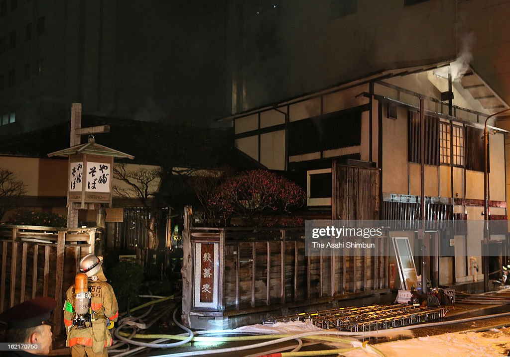 A firefighter looks up the smoke after the fire has been extinguished on February 19, 2013 in Tokyo, Japan. The restaurant started business in 1880, the 90-year-old building's roof and windows damaged.