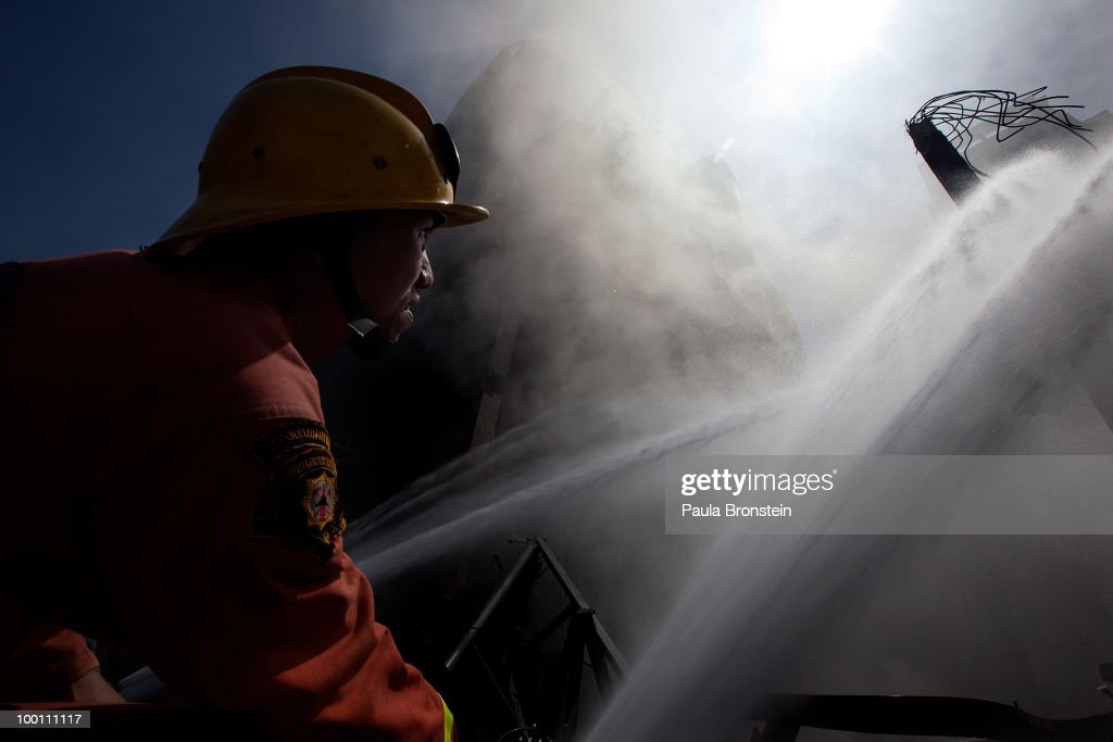 A firefighter mans the hose as smoke rises from a fire that is still smoldering at CentralWorld shopping mall, attacked by redshirt protesters venting their anger against the government on May 21, 2010 in Bangkok, Thailand. Thai Prime Minister Abhisit Vejjajiva says order has been restored to the capital Bangkok and throughout the country. A night-time curfew remains in place in Bangkok and 23 provinces across the country to prevent a resurgence of unrest as privincial anger grows over the assault on the Red-Shirt opposition . At least 44 people have been killed in clashes in which protesters clashed with military forces over a period of six consecutive days resulting in the end of the blockade and the surrender of Red-shirt leaders.
