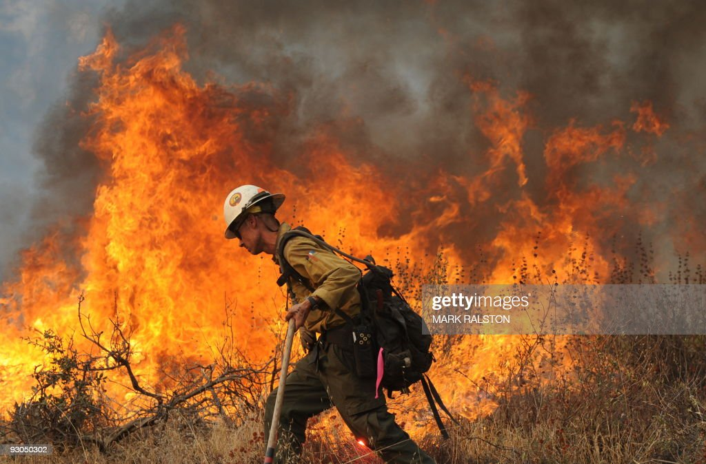 A firefighter monitors a fire in the suburb of Glendale on the outskirts of Los Angeles city on September 1 2009 A deadly wildfire roared out of...