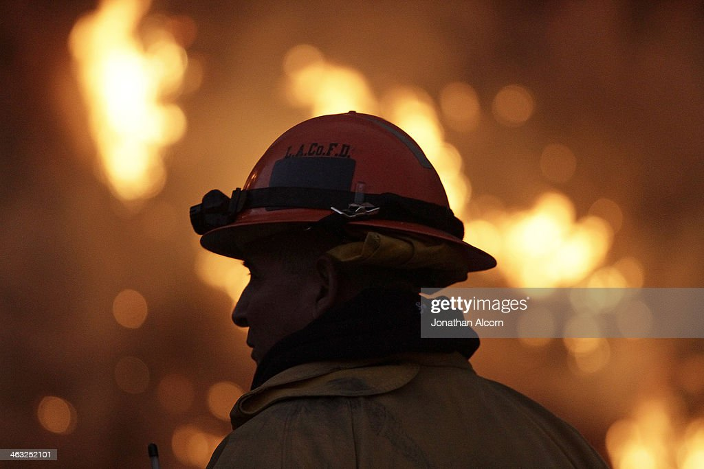 A firefighter monitors the Colby Fire burning for a second day on a hillside above Highway 39 in Azusa, California. Three men have been arrested and charged with starting the fire that has now destroyed 1,700 acres of land and several homes around Glendora and Azusa in the San Gabriel Valley, prompting officials to order evacuations for houses near the fire.