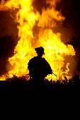 U.S. Army Sergeant monitors the flames of a fire around a canal in Tahwilla, Iraq, July 30, 2008. Soldiers set fire to the vegetation surrounding the canal to prevent extremists from continuing to use