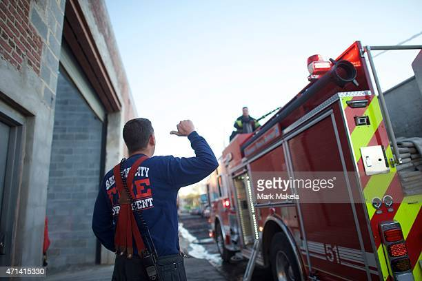 A firefighter motions to a fireman spraying water from a firetruck to extinguish the smoldering remains of a senior center set ablaze during night...