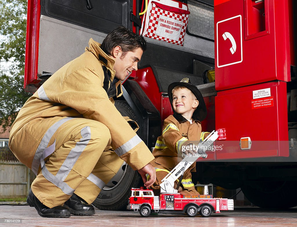 Firefighter playing with boy (4-5), smiling