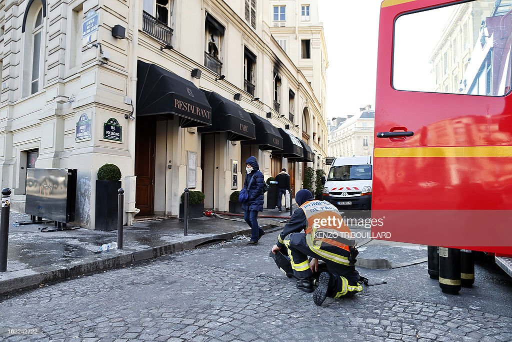 A firefighter prepares his equipment on February 21, 2013 before entering the restaurant of the Paris nightclub L'Arc after a fire, believed to have been set by arsonists, swept through it in the early morning.