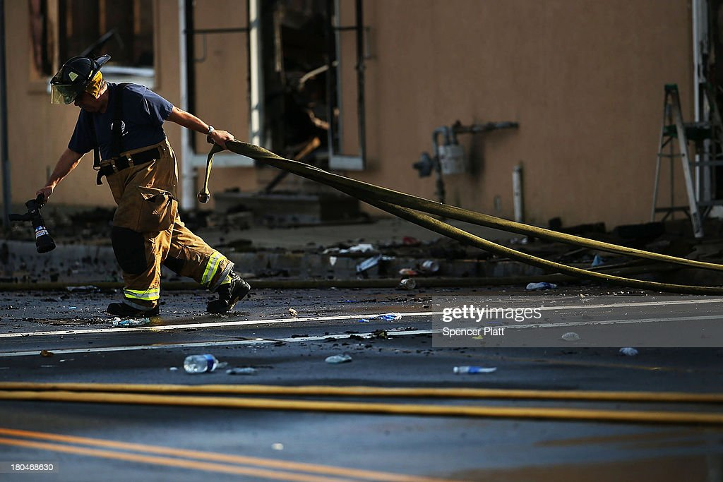 A firefighter pulls a hose at the scene of a massive fire that destroyed dozens of businesses along an iconic Jersey shore boardwalk on September 13, 2013 in Seaside Heights, New Jersey. The 6-alarm fire began in a frozen custard stand on the recently rebuilt boardwalk around 2:00 p.m. on Thursday, September 12, and quickly spread in high winds. While there were no injuries reported, many businesses that had only recently re-opened after Hurricane Sandy were destroyed in the blaze.