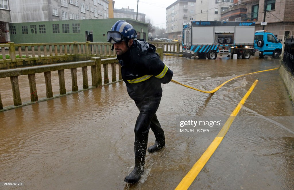 A firefighter pulls a hose in a flooded area next to the river Tea in Ponteareas, northwestern Spain, on February 13, 2016. / AFP / AFP or licensors / MIGUEL RIOPA