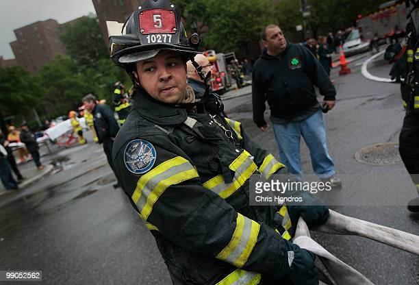 A firefighter pulls a hose line as firefighters work to douse a threealarm fire that broke out at 502 East 14th Street across from Stuyvesant Town in...