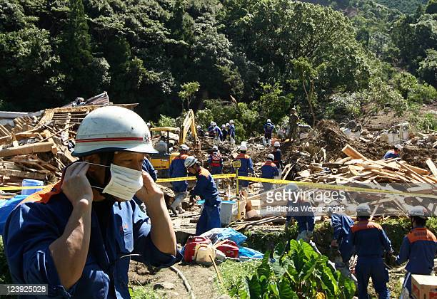 A firefighter puts a mask during a members of Ground SelfDefense Force firefighters and police officers continue the search for missing people among...