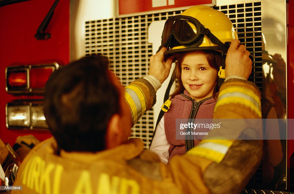 Firefighter Putting His Helmet on A Girl