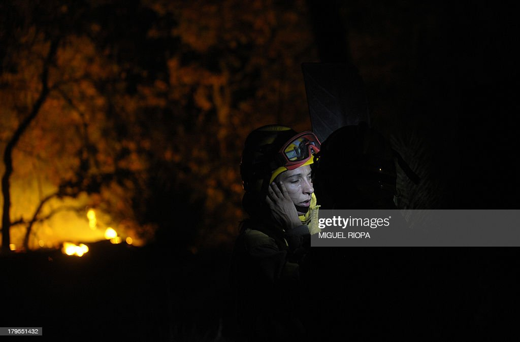 A firefighter reacts at the site of a wildfire in the village of Barbudo, some 40 km from Vigo, northwestern Spain, in the early hours of September 5, 2013.