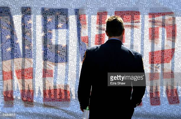 A firefighter reads the names of the victims of the 9/11 terrorist attacks written on a memorial that reads 'Never Forget' on the second anniversary...