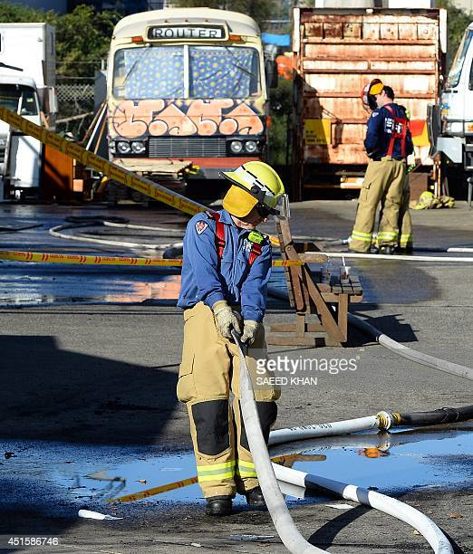 A firefighter removes a hose after a fire broke out at a warehouse in an industrial area in Sydney on July 2 2014 At least 15 people reportedly...