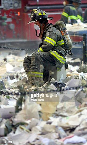 A firefighter rests in the area where the World Trade Center buildings collapsed September 11 2001 after two airplanes slammed into the twin towers...