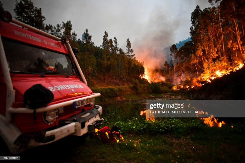 TOPSHOT - A firefighter rests next to fire combat truck during a wildfire at Penela, Coimbra, central Portugal, on June 18, 2017. A wildfire in central Portugal killed at least 25 people and injured 16 others, most of them burning to death in their cars, the government said on June 18, 2017. Several hundred firefighters and 160 vehicles were dispatched late on June 17 to tackle the blaze, which broke out in the afternoon in the municipality of Pedrogao Grande before spreading fast across several fronts. /