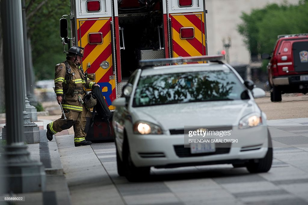 A firefighter returns to his truck on Pennsylvania Avenue near the northwest gate to the White House, during a security lockdown of the White House grounds May 30, 2016 in Washington, DC. / AFP / Brendan Smialowski