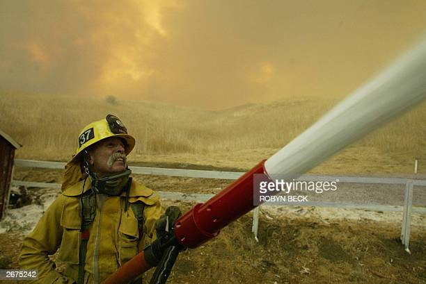 Firefighter Ron Bartolomei shoots foam onto historic buildings at Mentryville historic town in Santa Clarita in Los Angeles Country as flames crest...