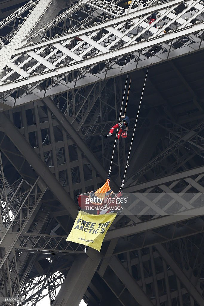 A firefighter ropes down to pick up a Greenpeace activist in a tent hanging from the Eiffel Tower on October 26, 2013 in Paris, to protest the custody of the 'Arctic 30', a group of Greenpeace activists charged with on hooliganism in the northern Russian region of Murmansk after their ship, the Arctic Sunrise, was seized by Russian security forces in a commando-style operation in Arctic waters following a protest at a Gazprom oil rig.