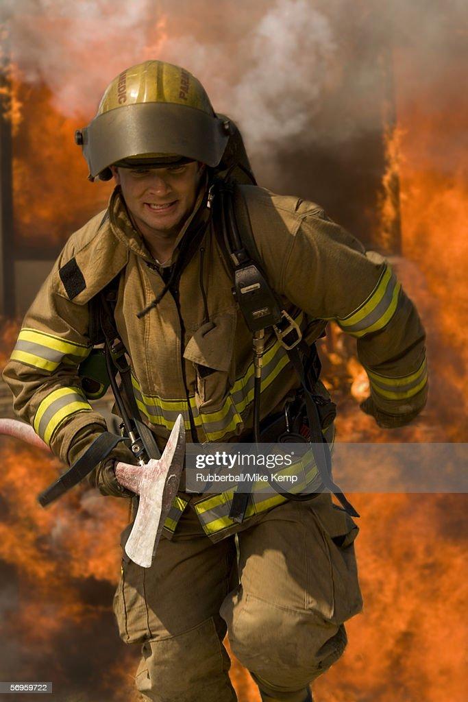 Firefighter running through fire holding an axe
