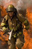 Firefighter running through fire holding an axe