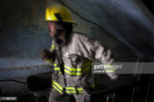 A firefighter runs out of an apartment building while attending to a flood caused by heavy rain on June 15 2009 in Kabul Afghanistan The Kabul Fire...