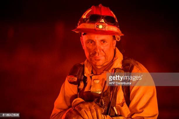Firefighter Sam Goodspeed of the Nevada City Fire Department looks towards approaching flames as the Detwiler fire rages on near the town of Mariposa...