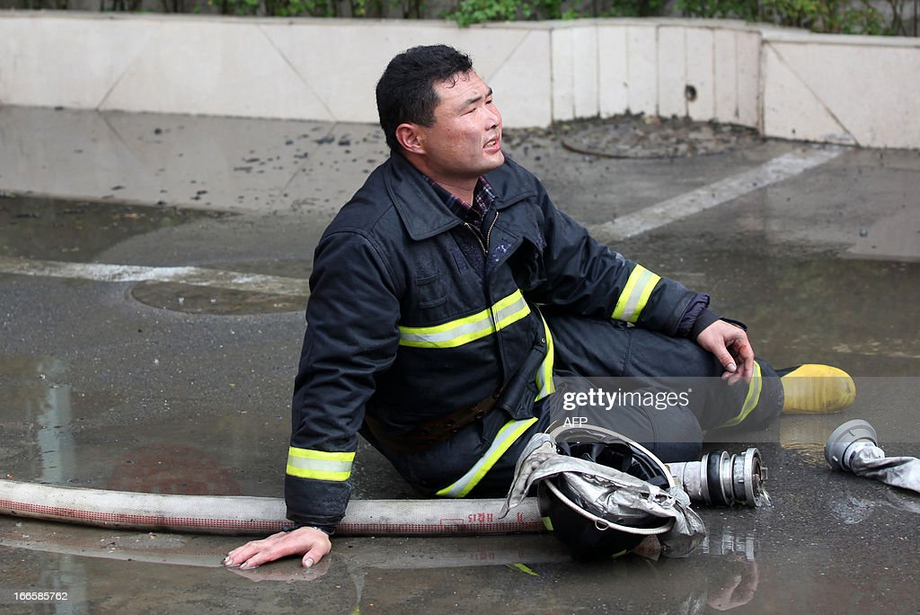 A firefighter sits on the ground as they worked to put out a fire in a hotel in Xiangyang, central China's Hubei province on April 14, 2013. The fire, started from an Internet cafe downstairs, resulted in 11 deaths and 50 injuries, local government reports annouced. CHINA