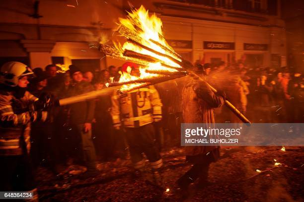 TOPSHOT Firefighter splash water on a man carry burning bundles of pinewood chips on their shoulders during the 'Chienbase' procession on March 5...