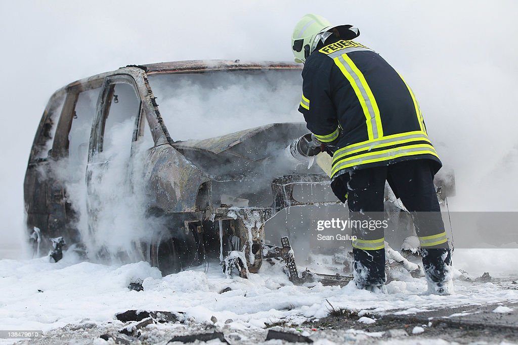 A firefighter sprays fire retardant into a burning car that had caught fire on the A2 highway towards Hanover on February 7, 2012 near Lehnin, Germany. The car blocked up traffic on the highway for several kilometers.