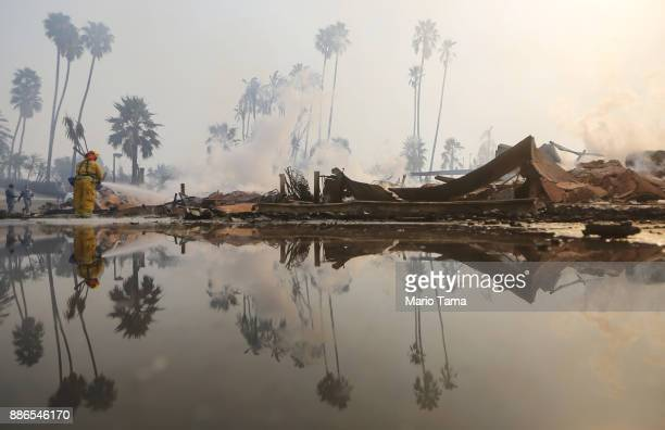 A firefighter sprays water at the remains of an apartment complex destroyed by the Thomas Fire on December 5 2017 in Ventura California Around 45000...