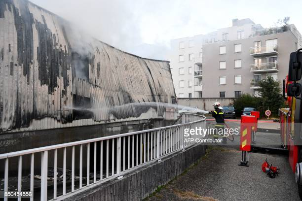 A firefighter sprays water on September 21 2017 in Grenoble eastern France on a burntout garage which contained about fifty vehicles of the French...
