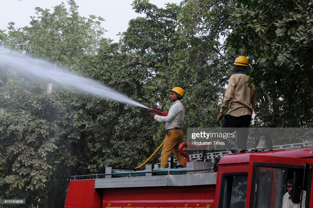 A firefighter sprinkles water on the trees to settle the dust as part of pollution control measures at sector 31/40 dividing road, on November 14, 2017 in Gurgaon, India. Delhi battled with severe air pollution on Tuesday as well. The Air Quality Index improved to an average reading of 308, even as the Delhi government extended the ban on entry of trucks. Here are the live updates of the situation in the National Capital Region.