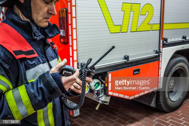 Firefighter Standing By Fire Engine