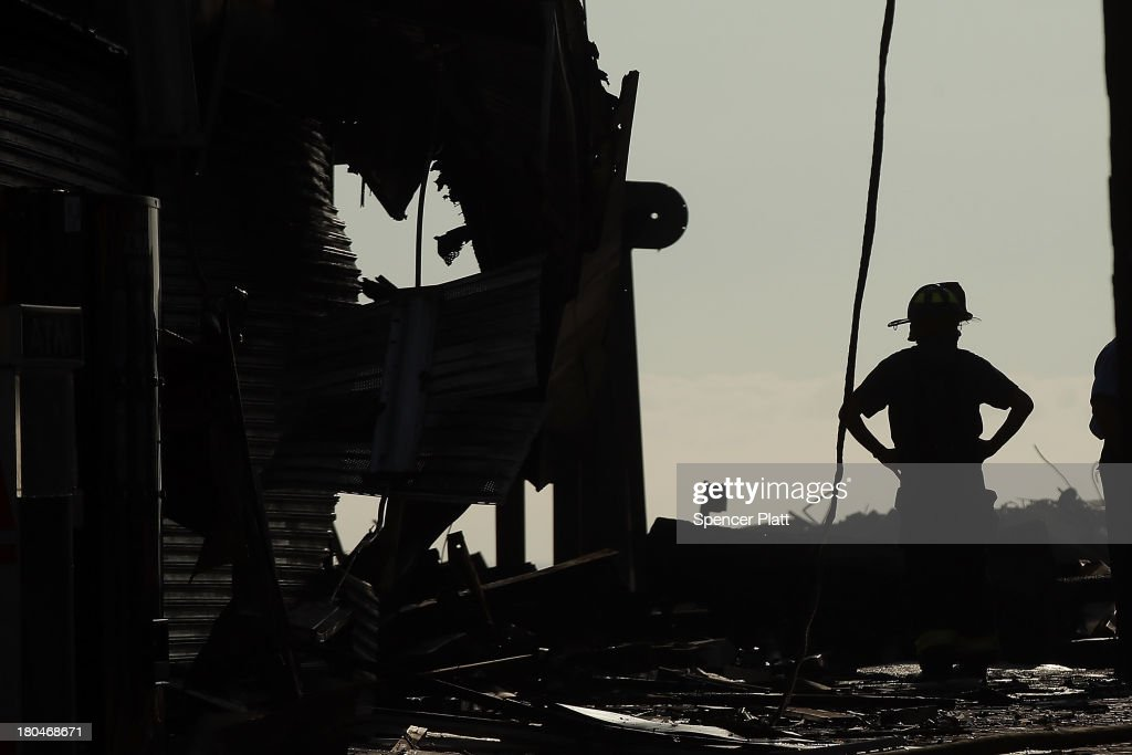 A firefighter stands at the scene of a massive fire that destroyed dozens of businesses along an iconic Jersey shore boardwalk on September 13, 2013 in Seaside Heights, New Jersey. The 6-alarm fire began in a frozen custard stand on the recently rebuilt boardwalk around 2:00 p.m. on Thursday, September 12, and quickly spread in high winds. While there were no injuries reported, many businesses that had only recently re-opened after Hurricane Sandy were destroyed in the blaze.