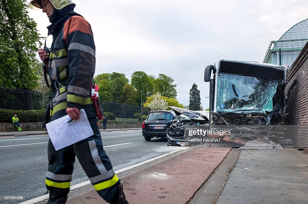 A firefighter stands at the site of an accident between a Brussels public transport MIVB/STIB bus and a van outside the Royal castle in Laken/Laeken, in northwest Brussels, on May 2, 2016, in which ten people were injured. The bus hit the wall surrounding the castle grounds after the van crashed into it injuring ten people, according to police. / AFP / Belga / HATIM KAGHAT / Belgium OUT
