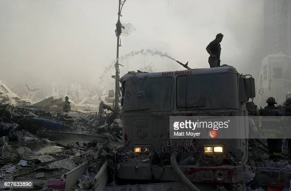 A firefighter stands atop a demolished fire truck at ground zero after the destruction of the World Trade Center on Sept 11 2001
