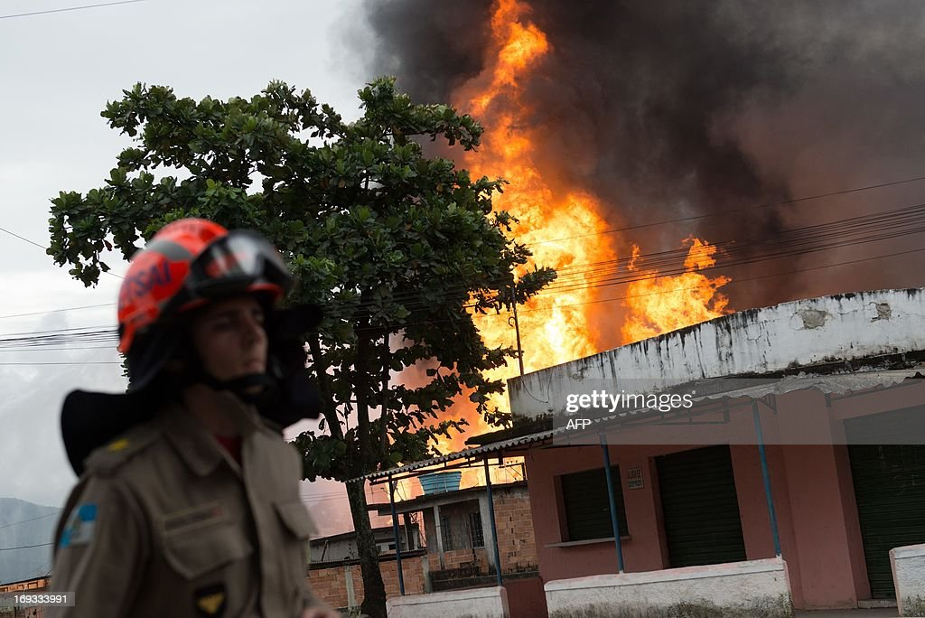 A firefighter stands by fuel tanks on fire in Duque de Caxias, Rio de Janeiro, Brazil, on May 23, 2013. A huge fire broke out Thursday at a fuel storage facility outside Rio de Janeiro and spread to nearby homes, but it was not immediately known if anyone was hurt, news reports said. AFP PHOTO/Yasuyoshi CHIBA