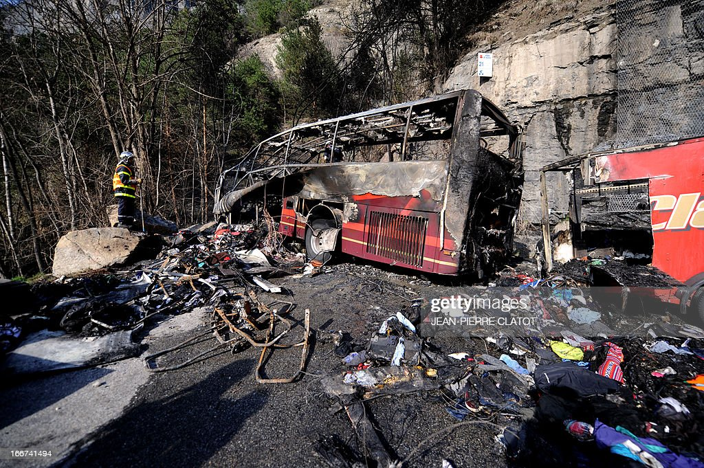 A firefighter stands by the wreckage of a bus transporting British citizens that crashed on April 16, 2013 near Bourg d'Oisans as they were leaving the French Alps resort of l'Alpe d'Huez. The accident killed at least one person, severely wounded three others, and slightly injured 21. In total, 53 people were aboard the bus, including two drivers.